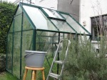 Washing a greenhouse. Not good to be in a hurry, as you don't want to fall off the stepladder through a glass roof! Keep one hand free to hold on to the frame all the time.