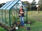 Áine tending some of the pea plants currently in the greenhouse to make the most of low light levels in winter.