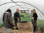 Dr Ollie Moore, Bruce Darrell, Emer and Grace O'Sullivan discuss keeping a polytunnel mproductive, with water tank in the background.