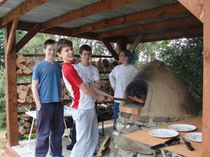 Voila - Conor Neville prepares to serve the first pizza from the new cob oven to be shared with the brothers Adam and Brian, while Áine checks on the seasoning wood supplies.